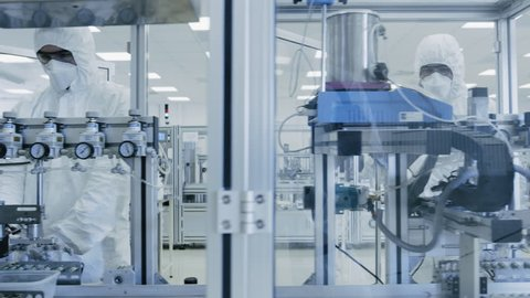 On a Factory Team of Scientists in Sterile Protective Clothing Work on a Modern Industrial 3D Printing Machinery. Pharmaceutical, Biotechnological and Semiconductor Manufacturing. Shot on RED EPIC 8K.