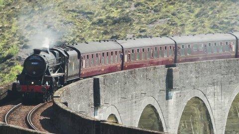 Glenfinnan, Scotland - May, 2018: View of Steam Train crossing Glenfinnan Viaduct Scotland, Pan Right