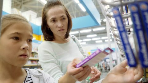 A girl with her mother chooses crayons in a supermarket. Purchase of school supplies.