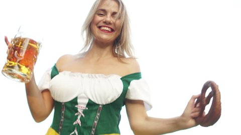 A beautiful dancing girl dressed in Oktoberfest costume of Bavaria holds a beer mug and a traditional Bavarian pretzel. The woman leans over the camera, the bottom view. Dance to Oktoberfest