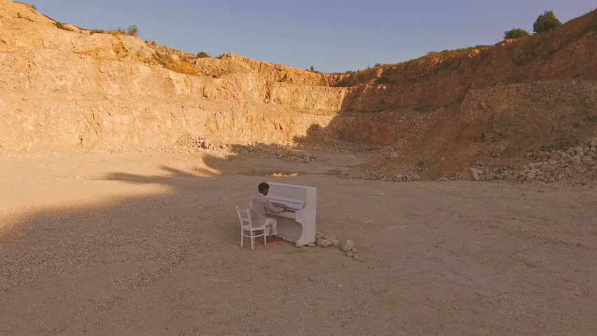 Young man plays on a white piano on a background of yellow cliff. Aerial view | Shutterstock HD Video #1014520724