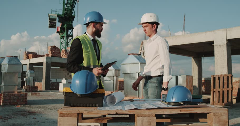 Two young engineers walking through construction site , background big crane , they wearing safety equipment. red epic | Shutterstock HD Video #1014527384