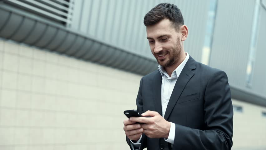 Young Attractive Man Chatting on his Smartphone with Interest. Typing a Message. Walking by the Big Industrial Building. Looking Satisfies. Smiling Sincerly. Classical Jacket. Stylish Clothes. | Shutterstock HD Video #1014544424