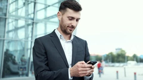 Young Attractive Businessman Standing near Big Modern Office Building. Typing a Message on his Smartphone. Looking Satisfied. Bearded Man Wearing Classical Suit. Business Lifestyle.