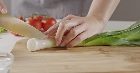 Close-up background with red ripe tomatoes, organic greens on white table. Chef in an apron slices green leek on a wooden cutting board for cooking a salad. Slow motion video in 4K