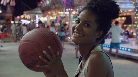 Young woman smiles at camera and throws a basketball at funfair.
