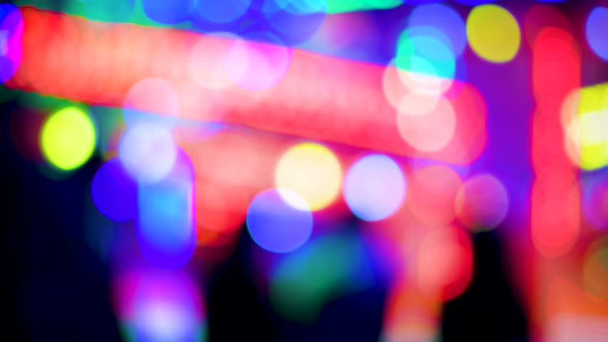 4K UHD Defocused funny atmosphere at the amusement park in megapolis with multiple colorful lights