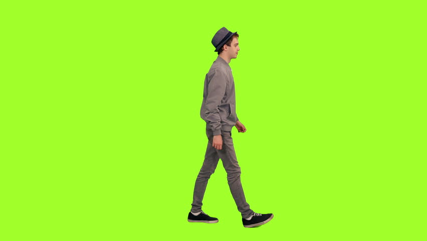 Young stylish man in hat walking on green chroma key background, Side view, 4k pre-keyed footage | Shutterstock HD Video #1014559784