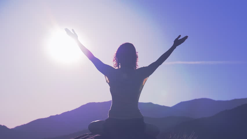 Yoga in the mountains at sunrise, woman pulls his hands to the sun | Shutterstock HD Video #1014563474