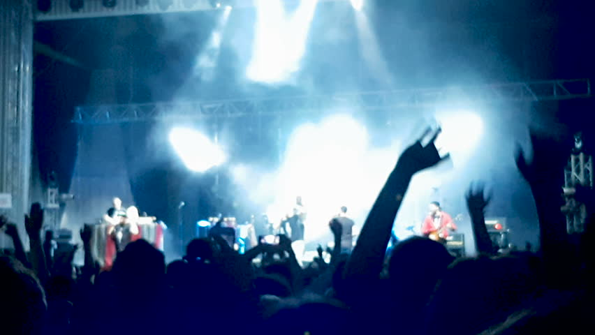 Crowd of people at a concert jumping and dancing with hands up while laser show is hitting the scene | Shutterstock HD Video #1014567764