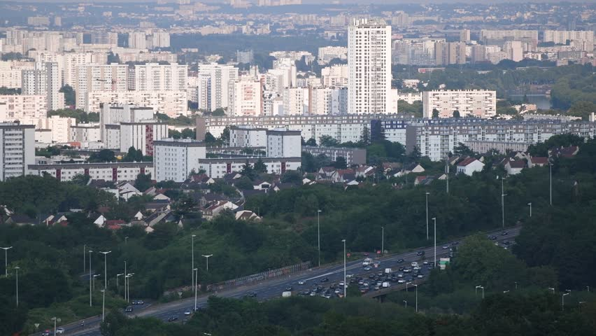 Aerial news report using drone with heavy traffic jam over the A15 highway autoroute peripherique with the city of Sannois, Paris in the background