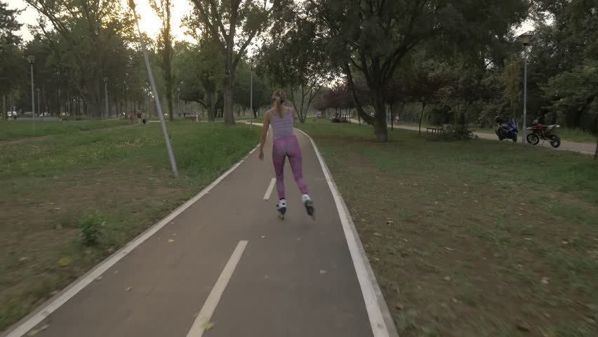 White handsom brown hair girl in tight violet pants woman riding roller skates on bike road in park, during summer golden hour