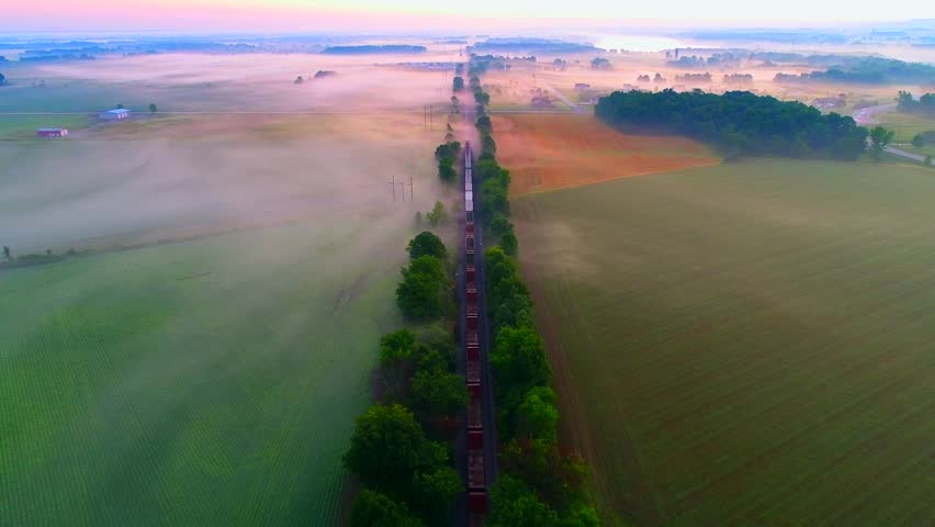 Freight train rolls across foggy rural landscape at sunrise with ethereal beauty, aerial view.