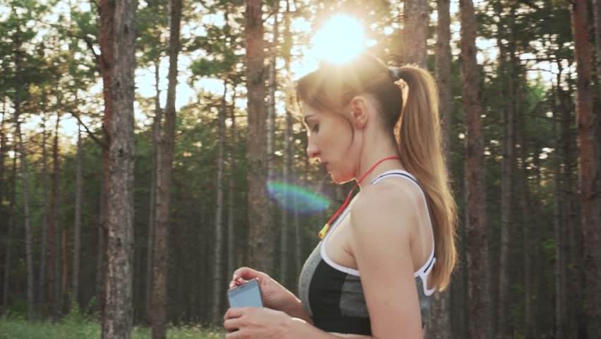 Sports woman inserts headphones into music player and starts training | Shutterstock HD Video #1014592784