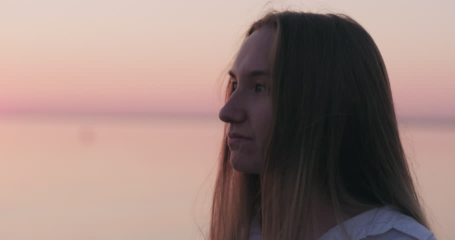 Slow motion handheld teenage girl stand on a beach at sunset and touching her hair #1014594884