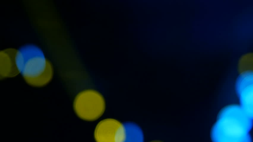 Blue and yellow light on the stage. Soffits shine at the concert. Luminous stage light flashes in the smoke