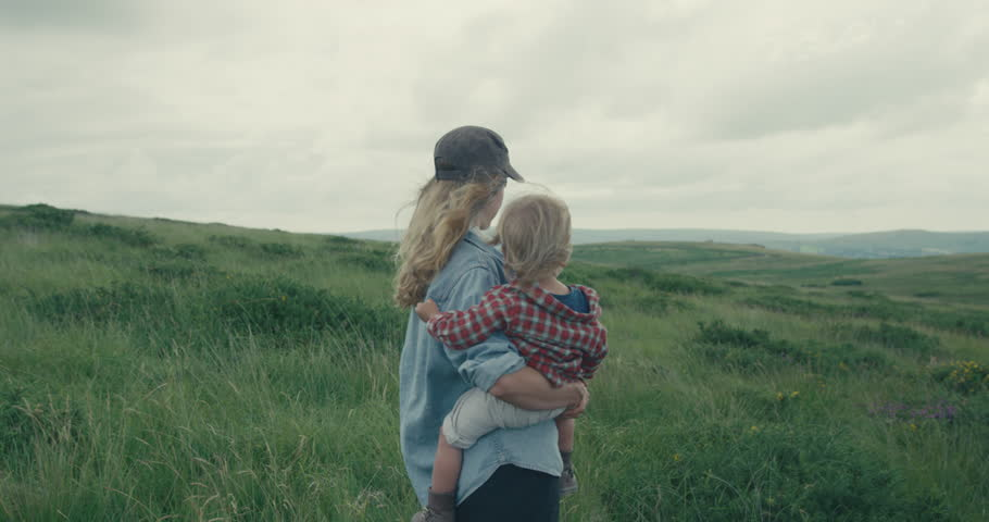 A young mother is standing on the moor with her toddler in her arms | Shutterstock HD Video #1014628574