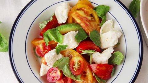 A woman cook prepares caprese salad, adding black pepper and basil leaves to finish