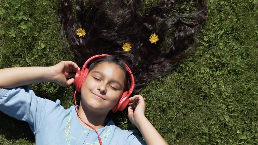 The girl lies on the grass in the park and listens to the music in the headphones.slow motion. HD   Shutterstock HD Video #1014671894