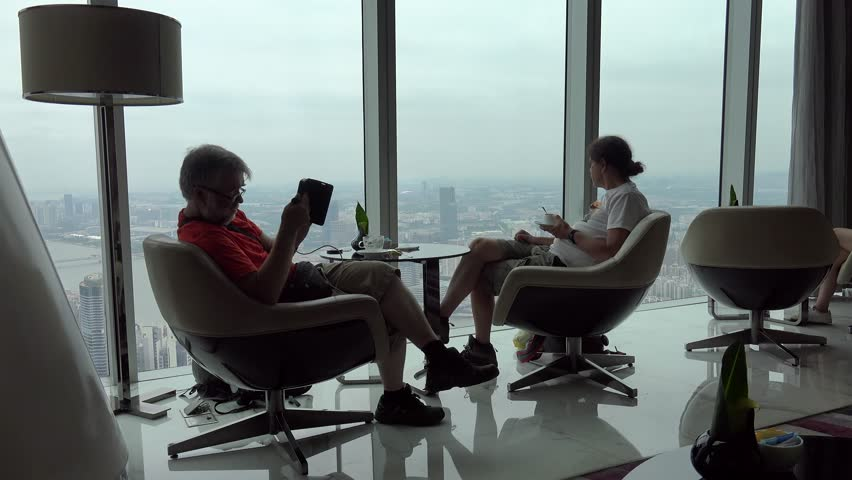 GUANGZHOU, - OCTOBER 19: Two guys are sitting by the panoramic window in the Four Seasons Hotel lobby bar at the 70th floor of West Tower Guangzhou. October 19, 2017 in Guangzhou, Guangdong, China   Shutterstock HD Video #1014691064