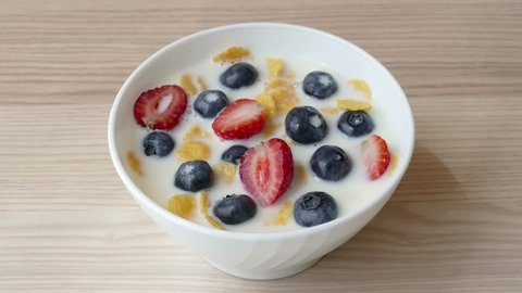 Cornflakes with natural milk, strawberries and blueberries for delicious breakfast or dessert. Healthy eating concept in stop motion animation
