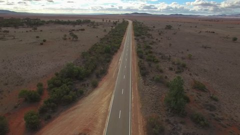 Forward flight low above rural road passing through desert landscape of South Australia