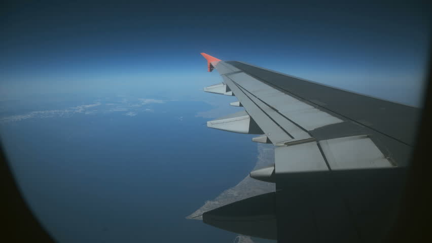 View through the airplane's window, wing, clouds, blue sky nature. 4K