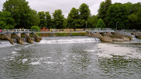 footage of a river weir or small waterfall. filmed from a river boat it shows the water falling over the weir into the river and lock.