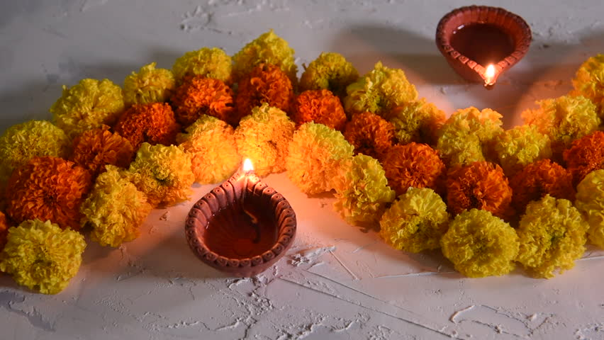 diwali diya with flower rangoli, sweets and gifts
