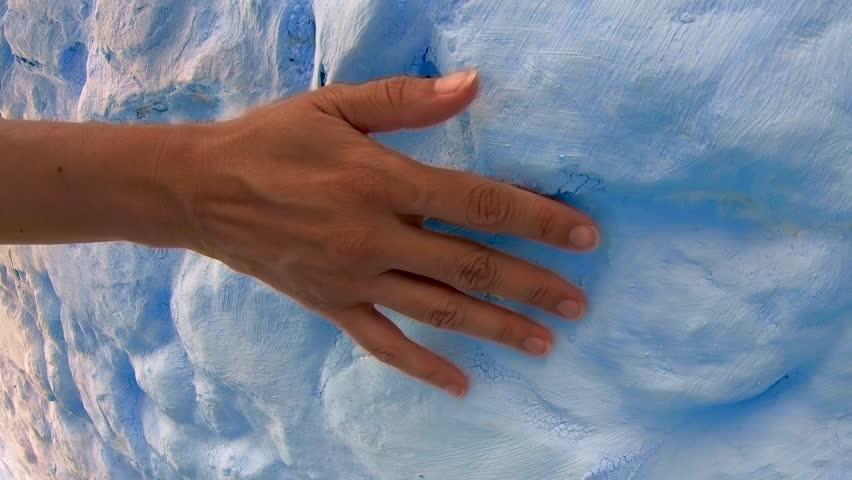 Woman walks and grazes hand on blue wall in Morocco.