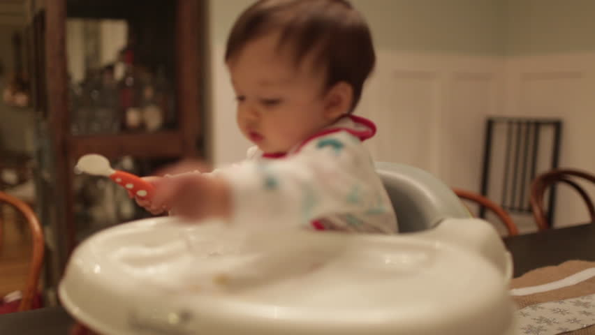 One Year Old Eating Puffs in High Chair   Shutterstock HD Video #1014769904
