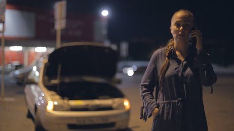 a young woman standing near a broken car at night on the road in the rain, calling on the phone, crying and swearing, asking for help.