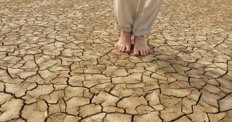 Steadycam shot of male feet going down cracked groung of lake dried because of ecological disaster. 4k steadycam
