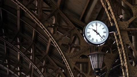 Clock on the old railway station among the metal structures.