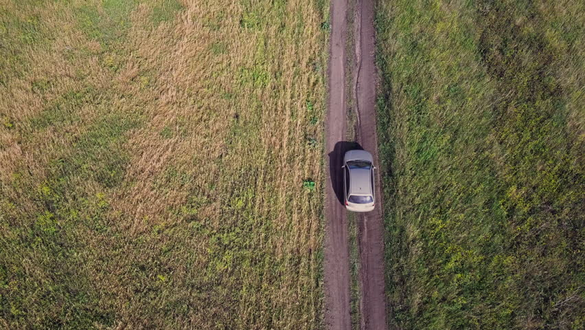 Aerial drone flight over the car moving on the country road, camera top down view, golden fields and green birches on the sides, the harvest season is coming, russian countryside #1014815774