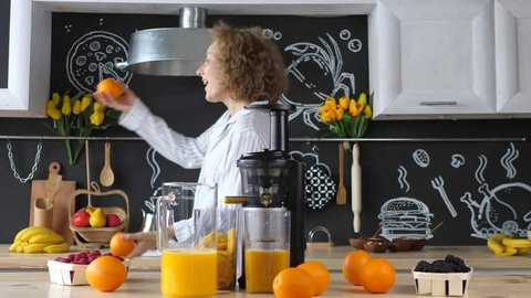 Happy Girl Dancing And Making Fresh Orange Juice At Kitchen