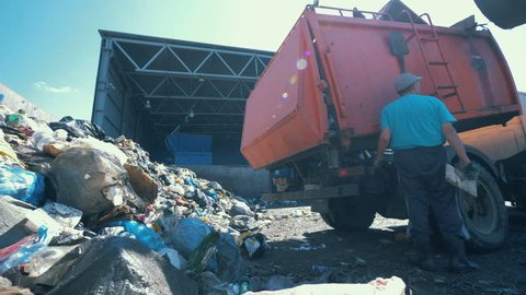 Litter is getting discarded from a truck in a scrapyard. Environmental pollution concept.