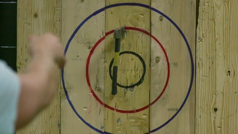 Man Throwing Axe and Hitting Wood Target in Slow Motion
