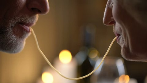 Romantic senior couple eating spaghetti and kissing, man and woman date dinner