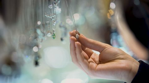 Female hand holding diamond pendant, jewelry assortment in luxury shopping mall