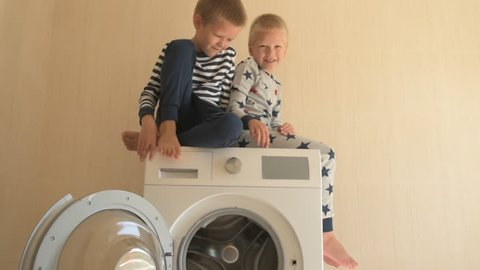 Parents bought new washing machine of new model latest generation. Children try to turn it on and wash soft toys. Three Happy boys are playing at home. Social assistance to large families.