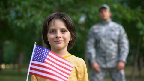 Adorable boy holding american flag, male soldier standing behind, safe future