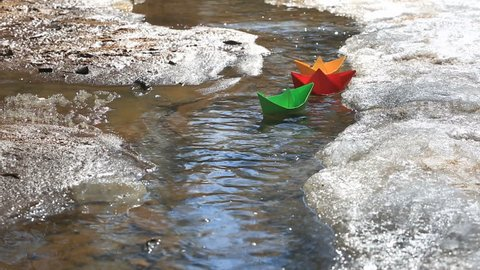 Colored paper boats floating on a stream from melting snow. Spring.