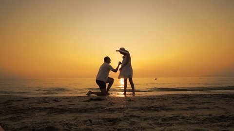 A man proposes on the beach at sunset, SLOW MOTION
