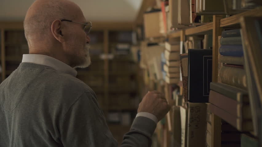 Mature male professor lawyer in glasses looking for a book on the bookshelves in the library. Portrait. Indoors. | Shutterstock HD Video #1014879364