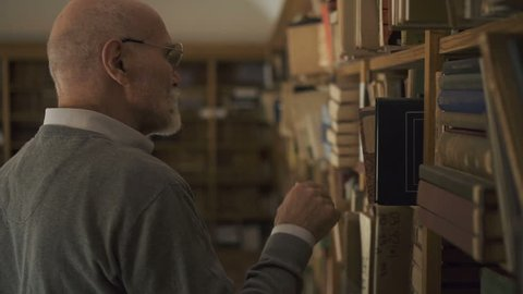 Mature male professor lawyer in glasses looking for a book on the bookshelves in the library. Portrait. Indoors.