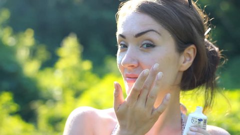 A young woman close-up is applying sunscreen on her face from the sun.