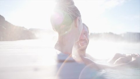 Geothermal spa. Young couple relaxing in hot spring pool in Iceland. people enjoying bathing in a blue water lagoon Icelandic tourist attraction, Video SLOW MOTION