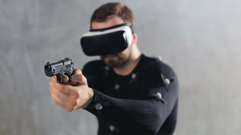 Athletic bearded man playing vr shooter game with virtual reality headset  testing motin capture suit while program recording the movement handgun  pistol shooting closeup on grey background studio