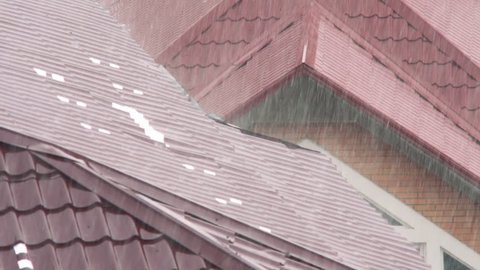 A heavy rain falls on the red metal roof of the house on a summer overcast day